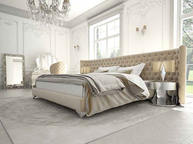 Sypialnia w stylu glamour może być utrzymana w jasnej tonacji kolorystycznej. Bardzo ważną rolę grają dodatki: pikowany zagłówek, ozdobny żyrandol z kryształami, wyszukana toaletka i lustro z rzeźbionymi ramami.