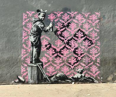 Banksy maluje polityczne murale w Paryżu. Na tym dziewczynka zasłania swastykę