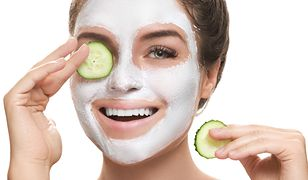 Woman with facial mask and cucumber slices in her hands on white background