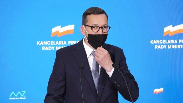 Mateusz Morawiecki poprawia maseczkę (fot. Kancelaria Premiera)