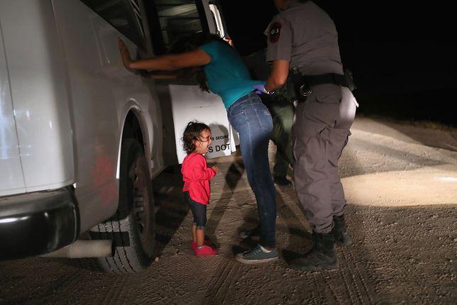 Funkcjonariuszka straży granicznej przeszukuje Hondurankę. U stóp matki stoi dwuletnia płacząca dziewczynka