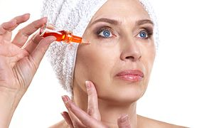 mature woman doing rejuvenation  spa procedure for face on white background