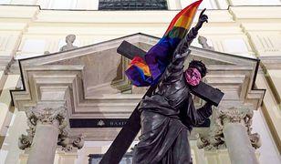 Tęczowe flaga LGBT na warszawskim pomniku przed Bazyliką św. Krzyża na Krakowskim Przedmieściu