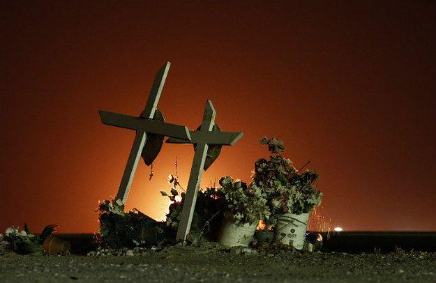 Krzyże przydrożne w Buttonwillow w Kalifornii na tle łun ognia z pól ropy łupkowej