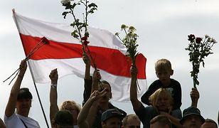 Białorusini wychodzą na ulice z białymi kwiatami