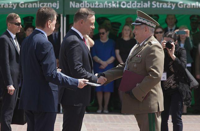 Prezydent Andrzej Duda w towarzystwie szefa MSWiA Mariusza Błaszczaka wręcza nominację komendantowi głównemu SG Markowi Łapińskiemu
