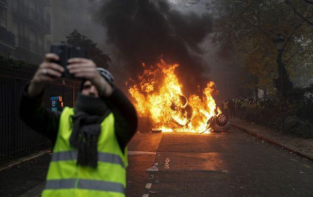 """Paryż.1 grudnia 2018 roku. Jeden z uczestników protestu """"żółtych kamizelek"""" robi selfie na tle płonącego samochodu"""