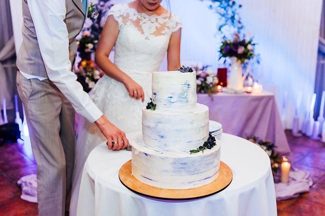 Para młoda krojąca tort weselny