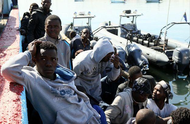 Migranci czekają w dokach Tripolisu po tym, jak ich łódź zatonęła niedaleko wybrzeża