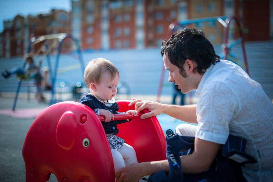 Ojciec z dzieckiem na placu zabaw