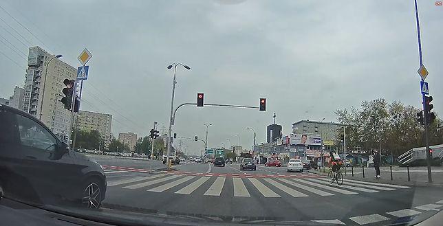 Rowerzysta przejeżdża przez ruchliwe skrzyżowanie na czerwonym świetle