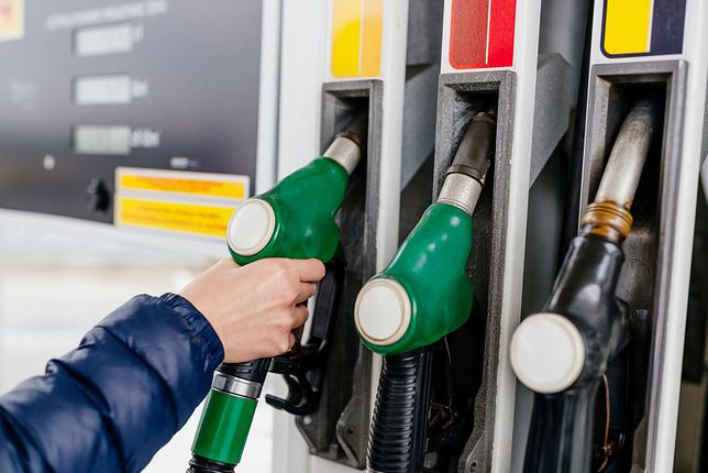 Woman holding a fuel nozzle on the gasoline station