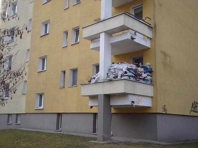 Balkon uginający się od stosu śmieci