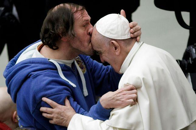 Papież Franciszek wycałowany przez wiernego podczas audiencji.