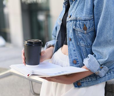 close up view of a diary and coffee in hands of woman outdoors