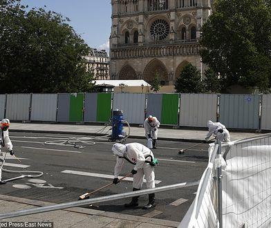 Pracownicy oczyszczają płynnymi chemikaliami teren przed Notre Dame pierwszego dnia po powrocie do pracy