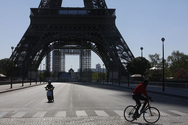A man rides his bicycle near Eiffel Tower in Paris, on April 14, 2020, during the lockdown in France to attempt to halt the spread of the novel coronavirus COVID-19.  (Photo by Mehdi Taamallah/NurPhoto via Getty Images)