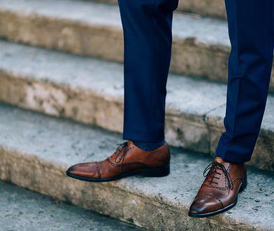 Brązowe buty idealnie pasują do granatowych spodni