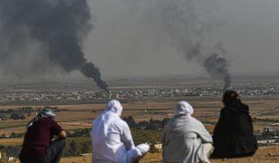 Atak Turcji na Syrię. Ludzie patrzą, jak dym unosi się z syryjskiego miasta Ras al-Ain, na zdjęciu wykonanym po tureckiej stronie granicy, w Ceylanpinar, 11 października br.