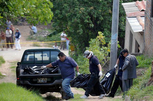 Policyjni śledczy zabiera ciała dwóch nastolatek i dwóch dorosłych kobiet zabitych prawdopodobnie przez członków gangu