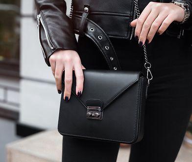 Czarna torebka na regulowanym pasku może być noszona na ramieniu lub na skos