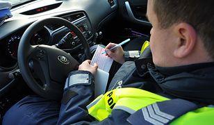 Policjant wypisuje mandat.