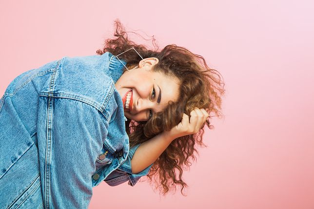 Beautiful young woman with curly hair in denim clothes. Trendy look, positive emitions, smile, copy space