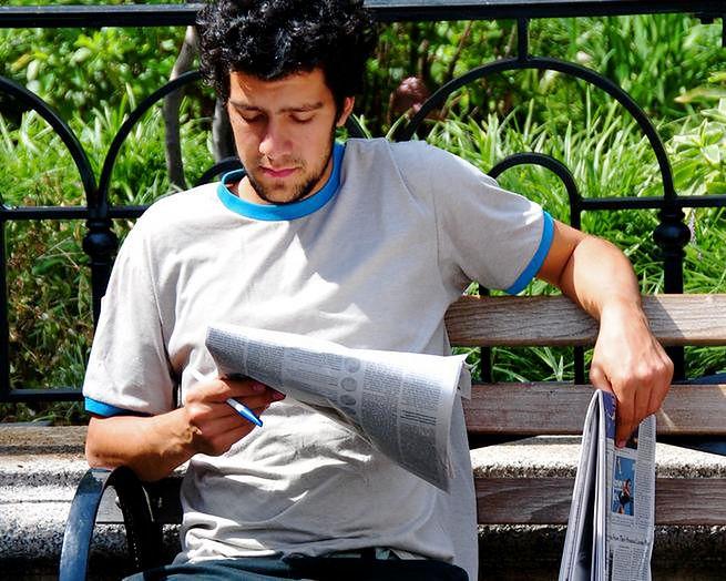 Mężczyzna czytający gazetę na ławce