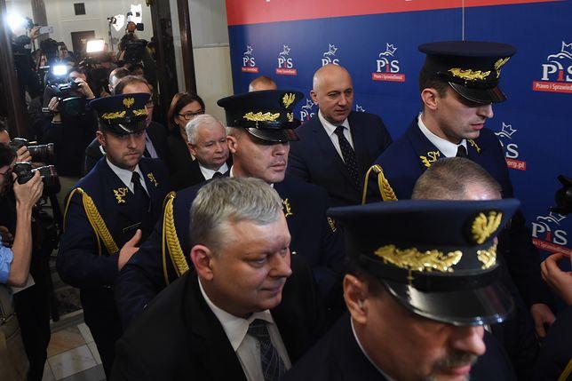 Czołowi politycy PiS w otoczeniu funkcjonariuszy Straży Marszałkowskiej