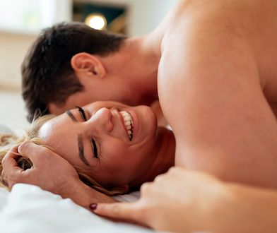 Sensual foreplay by couple in bedroom