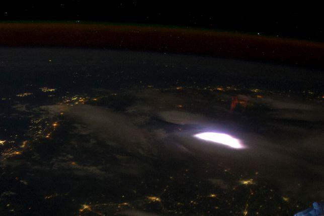 """Zdjęcie wykonane w 2012 roku z pokładu Międzynarodowej Stacji Kosmicznej. Nad widoczną na zdjęciu, rozświetlającą chmury błyskawicą, można dostrzec charakterystycznego czerwonego """"duszka"""""""