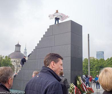 Arek Szczurek na szczycie pomnika rozwinął baner