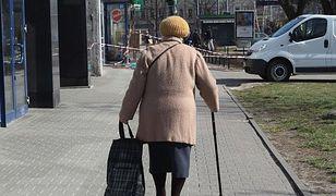 Starsza pani rozdaje ulotki pod sądem