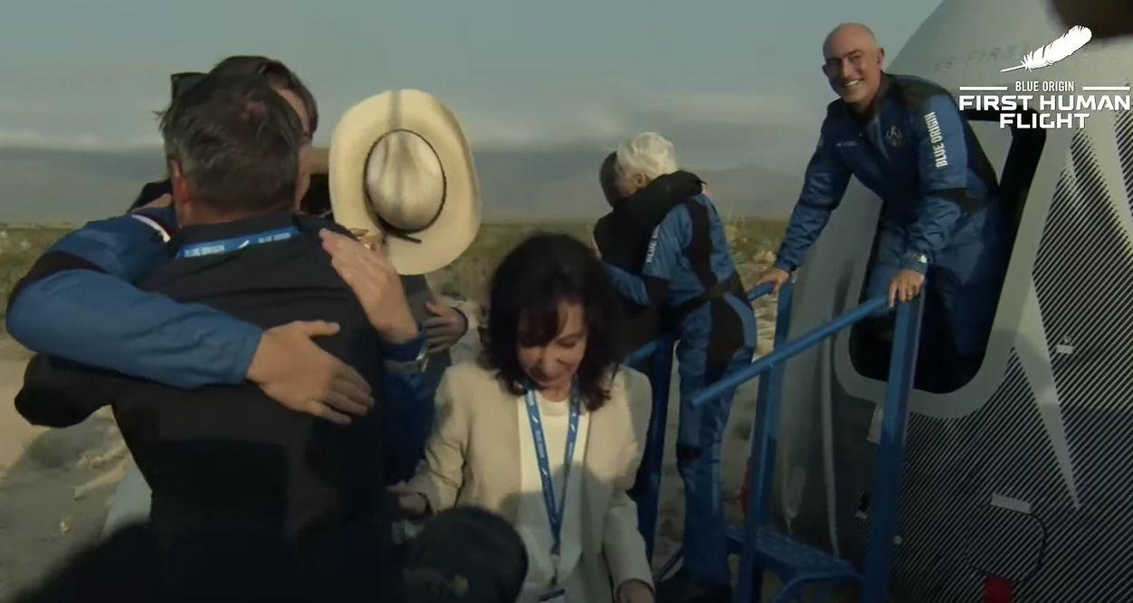 Jeff Bezos (z prawej) wychyla się z kapsuły statku kosmicznego, którym przed chwilą wrócił na Ziemię