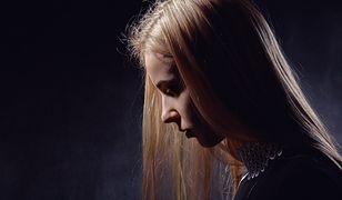 sad pensive girl profile on black background, toned image