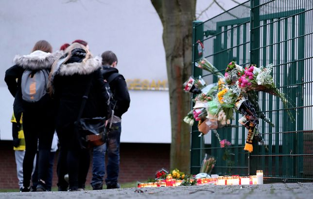 Przed szkołą koledzy zamordowanego ucznia ustawili znicze, a na ogrodzeniu umieścili wiązanki kwiatów