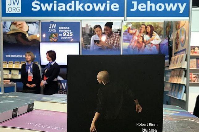 Mocne zdjęcie autorstwa Mariusza Szczygła. Stoisko Świadków Jehowy zestawione z książką o tej wspólnocie
