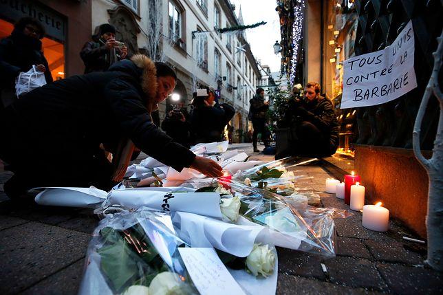 Dzień po tragicznych wydarzeniach w Strasburgu, w miejscach gdzie strzelał do ludzi napastnik, ludzie zapalają znicze i składają kwiaty