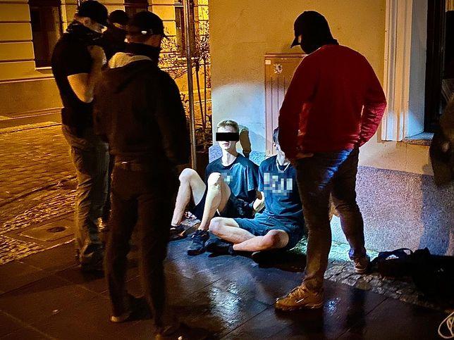 Zatrzymani dwaj mężczyźni w nocy siedzą na płycie starego rynku. Przy nich w półokręgu stoją policjanci po cywilnemu.(Fot: KWP Bydgoszcz)