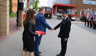Wiceminister Jarosław Zieliński uroczyście przekazuje kluczyki i dokumenty do wozu strażackiego