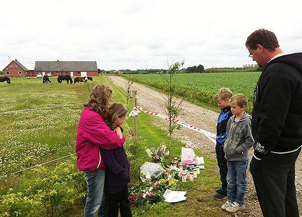 W pobliżu farmy ludzie składają kwiaty i znicze