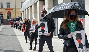 """Szczecin, 14.04.2020. """"Czarny Protest"""" przeciwko zaostrzeniu prawa aborcyjnego i kar za edukację seksualną. Protestujący ustawili się w kolejce do sklepu, aby nie łamać zakazu zgromadzeń z powodu epidemii"""