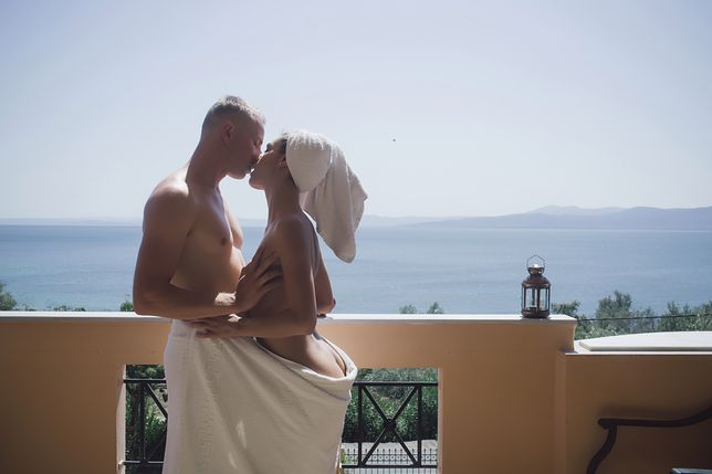 couple in love wrapped in a towel, hugging and kissing on the balcony