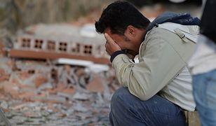 Mężczyzna na tle zniszczonego budynku w Amatrice