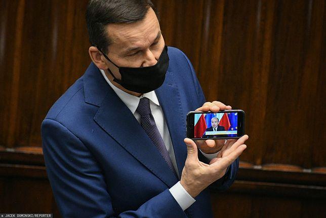 Premier Mateusz Morawiecki (na ekranie telefonu Borys Budka)