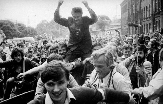Sierpień '80. Stocznia Gdańska. Robotnicy niosą na rękach nieznanego mężczyznę w średnim wieku.