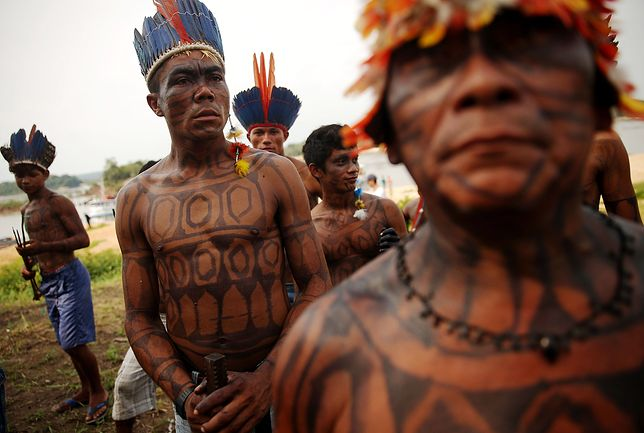 """SAO LUIZ DO TAPAJOS, BRAZIL - NOVEMBER 27: Members of the Munduruku indigenous tribe gather along the Tapajos River during a """"Caravan of Resistance'"""" protest by indigenous groups and supporters who oppose plans to construct a hydroelectric dam on the Tapajos River in the Amazon rainforest on November 27, 2014 in Sao Luiz do Tapajos, Para State, Brazil. Indigenous groups and activists travelled by boat from communities along the river to express resistance to the proposed 8.040- MW Sao Luiz do Tapajos mega-dam, which is one of a series of five dams planned in the region that will flood indigenous lands and national parks. The United Nations climate conference is scheduled to begin December 1 in neighboring Peru. (Photo by Mario Tama/Getty Images)"""