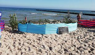 """Gałęzie i konary z wydm, a obok tabliczka z informacją o """"rezerwacji"""" na plaży w Ustroniu Morskim"""