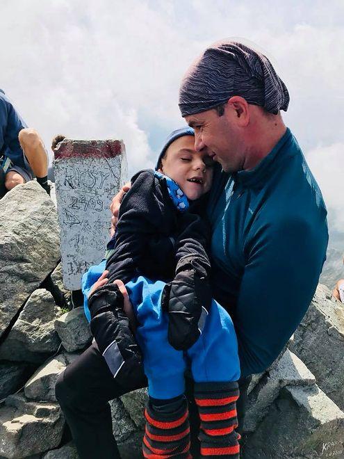 Szymon podróżuje po górach podczepiony do taty