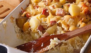 French cuisine: tartiflette potatoes with bacon and cheese close up in baking dish. Horizontal